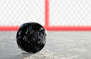 Hockey puck lying on a ice rink.