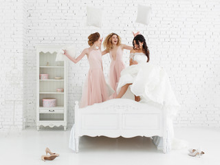 Bride and bridesmaids jump on the bed. White brick wall on background.