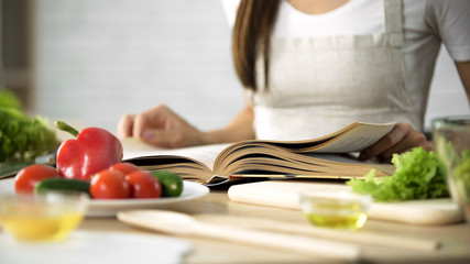 Housewife reading cooking book with fresh vegetables and kitchen tools on table