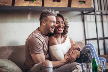 Two happy mixed race couple having fun at the coffee shop. Couple enjoying at a coffee shop, sitting at table and laughing.