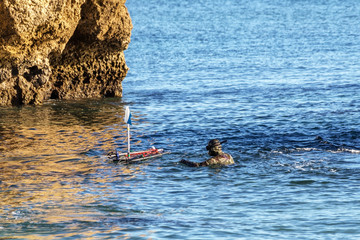 Underwater hunter, on surface, adjusts buoy with harpoons and crossbows.