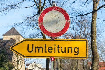 street sign with german text umleitung, in english detour