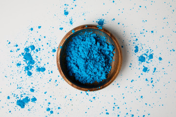 top view of blue holi paint in bowl isolated on white, Hindu spring festival