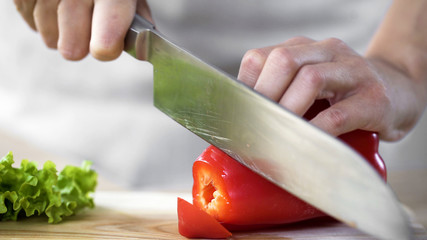 Female hands slicing red pepper by sharp kitchen knife during culinary show