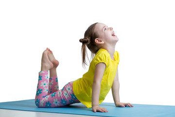 Child doing fitness exercises on mat isolated
