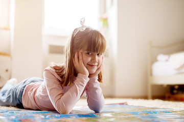 Portrait of beautiful little toddler girl lying on the carpet in her room and looking at the camera.
