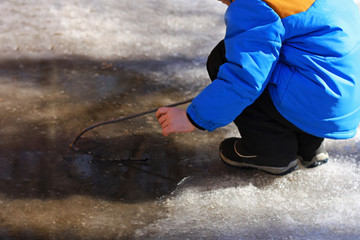 A child near a large puddle.