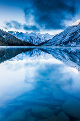Beautiful blue lake in the mountains. Flat mirror surface of the water under the clouds. The beauty of winter nature. A tourist Trip through the nature reserve of Altai.