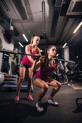 Attractive female personal trainer helping a girl with the bar without weights to do squat properly.