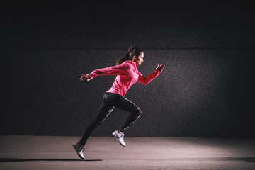 Side motion view of attractive sporty athlete running girl in sportswear at the street in front of the grey wall. Wall mural