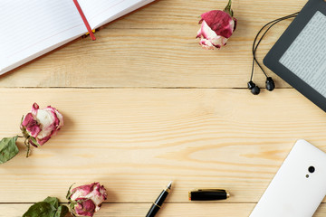 top view of wooden table with smartphone,  headphones, e-book; stylus pen, diary and dried roses and leaves