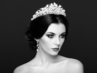 Fashion Portrait of Beautiful Woman with Tiara on head. Elegant Hairstyle. Perfect Make-Up and Jewelry. Red Lips. Black and White photo