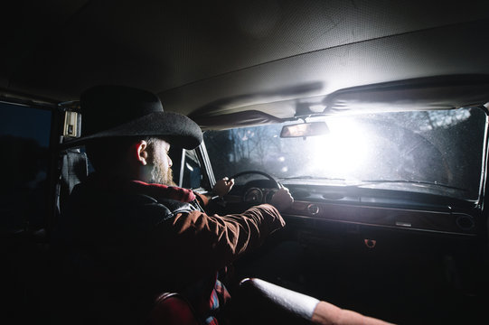 Stylish man driving old timer at night