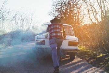 Man pushing broken vintage car