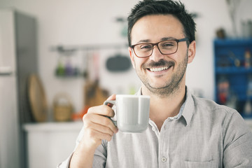 Happy smiling man looking camera and having cup of coffee