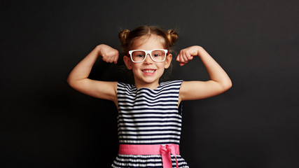 Pretty smiling child showing biceps muscles over dark background. Concept of power and success.