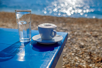 Cup of Coffee or Cappuccino on the blue wooden table at the beach. Summer relaxation on beach.