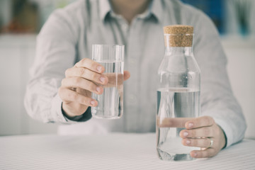 Young man having glass of water and holding bottle in kitchen