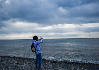 Girl taking pictures of the sea horizon