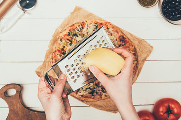 Close-up view of woman grating cheese on pizza on white wooden background