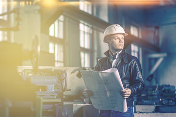 A young successful engineer with a drawing in his hands is standing in the territory of a modern factory.