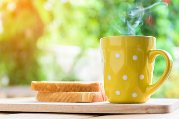 Good morning black coffee cup and bread on a wooden table in the sunrise background. breakfast and wake up
