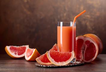 Glass of fresh grapefruit juice and cut fruits .