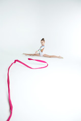 Rhythmic gymnastics caucasian blonde girl in dress for show performing athlete exercises with pink ribbon handling abilities showing flexibility and acrobat balance on white background isolated