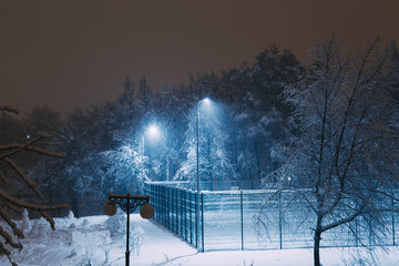Sports grounds in a park covered in deep snow, at night, street lighting is on.