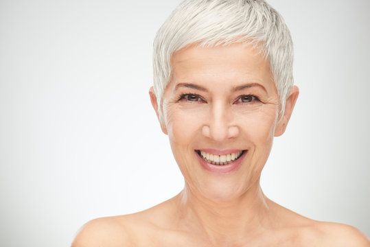 Portrait of beautiful senior woman in front of white background.