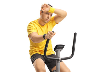 Tired young man exercising on a cross-trainer machine