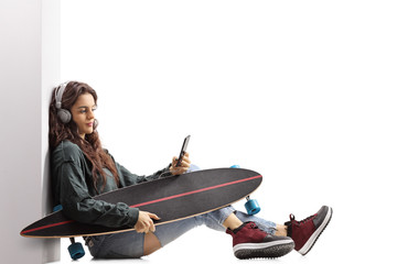 Teenage skater girl with a longboard leaning against a wall and listening to music on a phone
