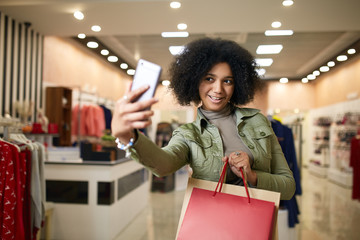 Cute african american woman taking selfie with shopping bags and smiling near clothing store. Black pretty girl taking photo on smartphone or talking on video call chat after visiting mall sale.