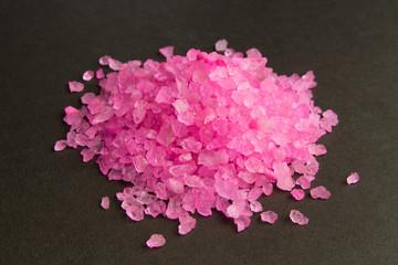 Bath salt. Pink crystals of salt on a dark background