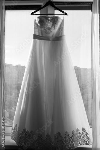 Wedding dress on hanger on the window. Black and white photo with ...