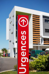 "Closeup of vertical red sign - ""Emergency"" (""Urgences"" in French)."