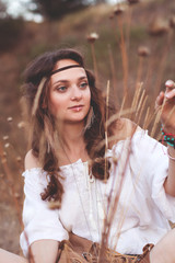 Charming girl in a Boho style on the background of a lake. Soft warm vintage photo color.