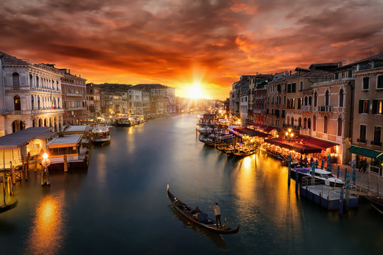 Romantischer Sonnenuntergang über dem Canal Grande in Venedig mit vorbeifahrender Gondel