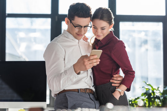 attractive young businesspeople in formal clothing having office romance and using smartphone together