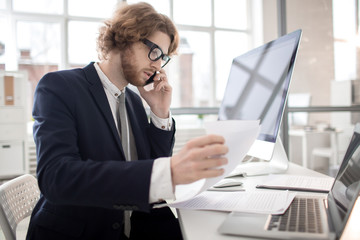 Young accountant looking through financial documents and talking to client by smartphone in office