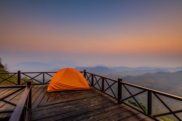 The orange hiker's  tent on the wooden terrace in  high mountain.