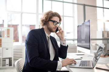 Serious businessman in suit speaking to colleague by smartphone while sitting by desk in office