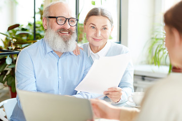 Happy modern senior couple with papers having talk to insurance agent in cafe
