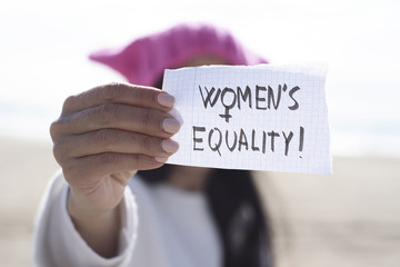 woman with a pink hat and the text womens equality