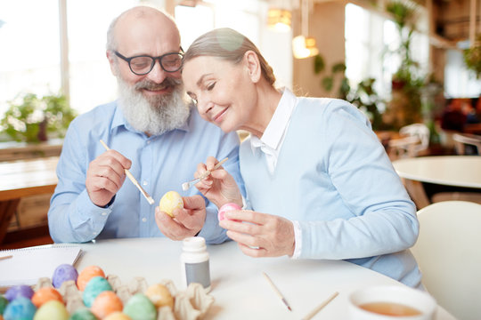Aged couple with eggs and paintbrushes sitting by table and sharing creative ideas for Easter