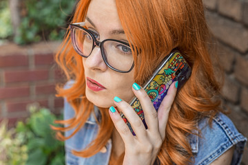 Beautiful redhead Caucasian girl talking on smart phone