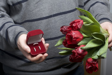 Gifts for loved ones. The men is holding a bouquet of red tulips in her hand. In the other hand, an open velvet box of red color, in which a ring and earrings.