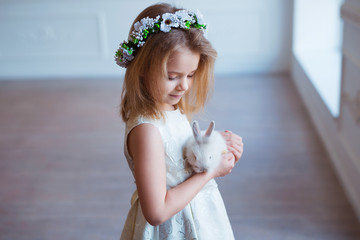 Cute little girl holding a bunny. Spring and easter portrait of beautiful child with rabbit.