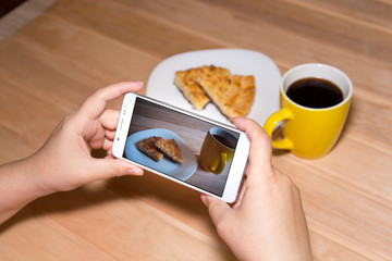 Using a mobile phone to photograph hot coffee and cookies on a wooden background with copy space. Photos of drinks and food for advertising or social media. Template.