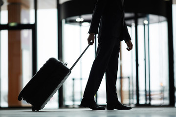 Silhouette of lowsection of business traveler with suitcase moving down modern airport
